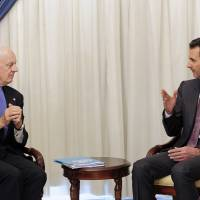 Syrian President Bashar Assad speaks with United Nations envoy to Syria Staffan de Mistura in Damascus in November 2014. | SANA / AP