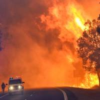Firefighters battle a massive blaze near Yarloop in Western Australia on Thursday. | AFP-JIJI