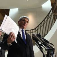House Homeland Security Committee Chairman Rep. Michael McCaul (right), accompanied by Rep. Richard Hudson, speaks to reporters on Friday about the arrest of two Iraqi-born men who came to the U.S. as refugees and were indicted on terrorism-related charges by federal authorities. McCaul is holding a copy of one of the indictments. | AP