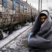 A migrant wrapped in a blanket waits with other migrants and refugees to board a train heading to the border with Croatia at the train station in Presevo, on Tuesday, after crossing the Macedonian border into Serbia. More than 1 million migrants reached Europe in 2015, most of them refugees fleeing war and violence in Afghanistan, Iraq and Syria, according to the United Nations refugee agency. | AFP-JIJI