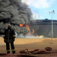 A Libyan fireman stands near an oil storage tank in the northern Ras Lanouf region on Jan. 23 after it was set ablaze earlier in the week during attacks launched by Islamic State group jihadis to seize key port terminals. | AFP-JIJI