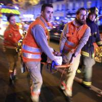 A woman is evacuated Nov. 13 from the Bataclan concert hall after a shooting in Paris. In a poll conducted by the Associated Press and the Times Square Alliance, 64 percent of those polled believe the attacks on Charlie Hebdo and the Jewish market, then the Bataclan concert hall and other city sites, were among the very or extremely important news events of 2015. | AP