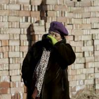 Manager Han Fengge stands outside her closed brick factory in a village on the outskirts of Beijing on Jan. 18. | REUTERS