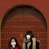 Women wearing protective masks visit the Temple of Heaven park in Beijing last month. | REUTERS