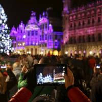 A tourist takes a picture during a light show on Brussels' Grand Place on Thursday after Belgian police held three people for questioning as part of an investigation into an alleged plot to carry out an attack in the capital on New Year's Eve. | REUTERS