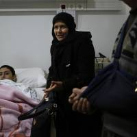 Pro-government Syrian student Hani Ali Hassan, 19, and his mother, Khadijah Sheikh Haidar, who were evacuated from the besieged Syrian village of Foua, speak during an interview Dec. 30 with the Associated Press in a hospital south of Beirut run by the militant Hezbollah group. | AP