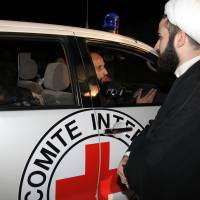 Ambulances of the International Committee of the Red Cross (ICRC) arrive as a convoy carrying Shiite residents from the towns of Foua and Kefraya drive out of Beirut International airport on Dec. 29. At least 120 people, including rebels and some civilians, crossed from the last rebel bastion on the Syrian border into Lebanese territory with Zabadani residents expected to fly from Beirut to Turkey, before traveling back into opposition-held areas in Syria, said Rami Abdel Rahman, head of the Syrian Observatory for Human Rights. | AFP-JIJI