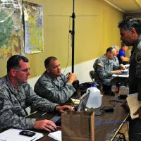 Senior Master Sgt. Gregory Kassa (left) and Maj. David Stilli, both of the Air National Guard's 194th Wing, confer last June with a helicopter pilot from the Snohomish County Sheriff's Department at the Mason County Fairgrounds in Shelton, Washington, as part of exercise Evergreen Tremor to prepare for a Cascadia Subduction Zone earthquake. For the past few years emergency officials in the Pacific Northwest have been drafting detailed contingency plans for the day a mega-quake and tsunami hit the region. | 2ND LT. HANS ZEIGER / WASHINGTON STATE ARMY NATIONAL GUARD VIA AP