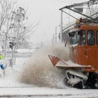 A maintenance tram clears tracks during a blizzard in Bucharest Sunday. Large areas of Romania are affected by heavy snowfall and blizzards that disrupted road and railway traffic. | AP
