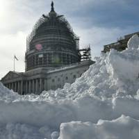 The U.S. Capitol rises above a large mound of snow cleared from the East Front on Monday in Washington, D.C.   AFP-JIJI