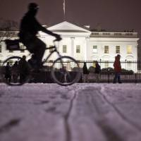 A bicyclist rides past the White House during evening snowfall in Washington Wednesday. As Washington prepares for this weekend's snowstorm, now forecast to reach blizzard conditions, a small clipper system pushed through the region Wednesday night causing massive delays and issues on the roads. | AP