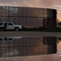 A jogger runs along the border fence in Hidalgo, Texas. | AP