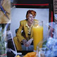 A poster with David Bowie's face is seen at a memorial outside of the apartment building where he had a home in New York on Monday. | AFP-JIJI