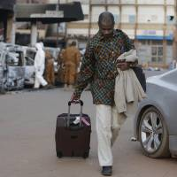 A guest leaves the Splendid Hotel with luggage, in Ouagadougou Sunday. The overnight seizure of a luxury hotel in Burkina Faso's capital by al-Qaida-linked extremists ended Saturday. | AP