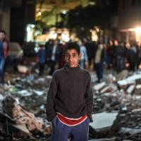 An Egyptian boy stands at the scene of a bomb blast in a main street in Giza on Thursday. | AFP-JIJI