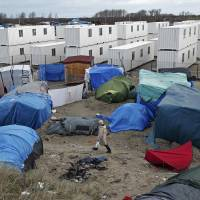 A migrant walks among tents in a makeshift camp as containers are put into place to house several hundred migrants living in what is known as the 'Jungle,' a squalid sprawling camp in Calais, northern France, Monday. | REUTERS