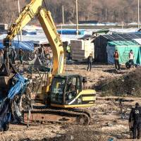 A worker uses an excavator Wednesday to clear a zone where makeshift shelters were set up in the migrant shantytown on the outskirts of Calais known as the 'Jungle' where thousands are trying to make their way across the English Channel. A prefectoral decree posted Tuesday gave people 24 hours to leave the premises of a 100-meter-wide strip of land in the 'Jungle.' | AFP-JIJI