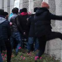 A video grab made Sunday shows dozens of migrants breaking a fence to approach a moored ferry in the northern French port of Calais on Saturday in a bid to reach Britain before police removed them from the ship. The boarding came after some 2,000 people protested nearby over living conditions in a notoriously squalid camp known as 'the Jungle.' | TARANIS NEWS / AFP-JIJI