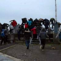 A video grab made Sunday shows dozens of migrants running toward a moored ferry in the northern French port of Calais. | TARANIS NEWS / AFP-JIJI