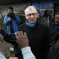 Denis Gaudin, subprefect of Calais, visits the 'Jungle' squalid sprawling camp in Calais, northern France, Monday. | REUTERS