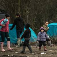 Migrants' children walk through the migrants camp of Grande-Synthe, near Dunkirk, on Wednesday, where almost some 2,500 migrants and refugees live, mostly Iraqi Kurds and Syryans. Authorities in the northern French port of Calais were struggling to move hundreds of migrants into refitted shipping containers ahead of plans to bulldoze part of the notorious 'Jungle' camp. | AFP-JIJI