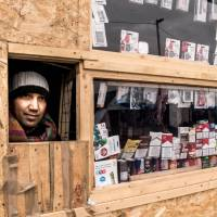A Pakistani migrant looks out of his shop at the migrants' camp known as the 'Jungle' on Monday in the northern French port city of Calais. | AFP-JIJI