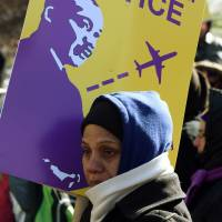 A New York airport worker demands higher wages while attending a protest near LaGuardia Airport on Jan. 18, Martin Luther King Day. | AFP-JIJI