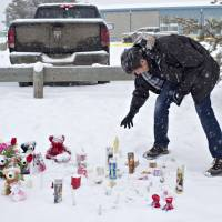 A resident of La Loche, Saskatchewan, pays his respects on Saturday to the victims of a Friday school shooting. | JASON FRANSON / THE CANADIAN PRESS VIA AP