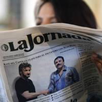 A woman reads La Jornada newspaper in Mexico City, on Sunday that shows a picture of drug lord Joaquin Guzman, aka 'El Chapo' shaking hands with U.S. actor Sean Penn. The Hollywood-worthy recapture of 'El Chapo' took a stunning turn Sunday as authorities sought to question Penn over his interview with the Mexican drug kingpin. A federal official told AFP that the attorney general's office wants to talk with Penn and Mexican actress Kate del Castillo about their secretive meeting with Guzman in October, three months before his capture on Friday. | AFP-JIJI