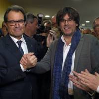 Catalan regional caretaker President Artur Mas (left) shakes hands with the current mayor of Gerona, Carles Puigdemont, who will be the candidate for the Catalan regional presidency after Mas announced that he will not seek a new term at the headquarters of the Convergence party in Barcelona on Saturday. | AFP-JIJI