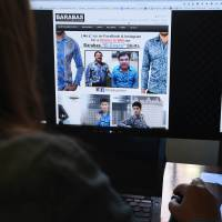 A woman looks at the homepage of the clothing house Barabas, which features a photo of Mexican drug lord Joaquín Guzmán Loera 'El Chapo' on Tuesday in Los Angeles. The company's website barabasmen.com features the shirt the Mexican fugitive was wearing at the meeting with U.S. actor Sean Penn, calling it the 'El Chapo' shirt. The shirt's official names is Barabas 'Fantasy' Men's Button Down Shirt and is priced at $128. | AFP-JIJI