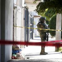 A soldier keeps watch outside the house where five people were shot dead during an operation to recapture the world's top drug lord, Joaquin 'El Chapo' Guzman, at Jiquilpan Boulevard in Los Mochis, in Sinaloa state, Mexico, Sunday. | REUTERS