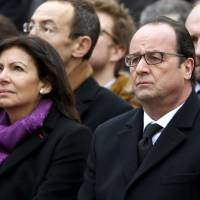 French President Francois Hollande and Paris Mayor Anne Hidalgo attend a ceremony at Place de la Republique square to pay tribute to the victims of last year's shooting at the French satirical newspaper Charlie Hebdo, in Paris Sunday. France this week commemorates the victims of last year's Islamist militant attacks on satirical weekly Charlie Hebdo and a Jewish supermarket with eulogies, memorial plaques and another cartoon lampooning religion. | REUTERS