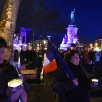 Two women hold French flags and candles bearing the inscription 'Stand' near the illuminated statue of the republique after a remembrance rally to mark a year since 1.6 million people thronged the French capital in a show of unity after the attacks on the Charlie Hebdo newspaper and a Jewish supermarket. Just as it was last year, the vast Place de la Republique will be the focus of the gathering as people reiterate their support for freedom of expression and remember the other victims of what would become a year of jihadi outrages in France, culminating in the Nov. 13 coordinated shootings and suicide bombings that killed 130 people and were claimed by the Islamic State group. | AFP-JIJI
