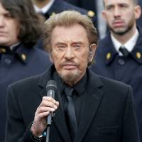 French rock star Johnny Hallyday sings among an army choir during a ceremony to honor the victims of the Islamic extremist attacks, at Place de la Republique in Paris Sunday. French President Francois Hollande and other dignitaries are holding a special ceremony to honor all those killed in Islamic extremist attacks around Paris in 2015, a year when the European way of life was targeted time and again with deadly consequences. | YOAN VALAT, VIA AP POOL
