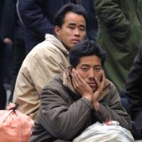 Migrant workers wait for a train at the main station in Beijing. | BLOOMBERG NEWS