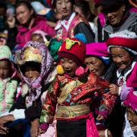 Tibetan children watch a dance festival at the Ganden Sumtsenling Monastery in China's Yunnan Province on Jan. 5. Children born in the Year of the Monkey are thought to be clever, potentially representing a windfall for China's population and for companies that target parents. | AFP-JIJI