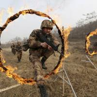 People's Liberation Army soldiers jump through burning hoops during training in Tianshui, Gansu province, on Jan. 6. | REUTERS
