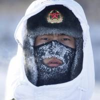 A soldier of China's People's Liberation Army (PLA) takes part in training in temperatures below minus 30 degrees Celsius at the country's border with Russia in Heihe, Heilongjiang province, on Wednesday.   CHINA DAILY / REUTERS