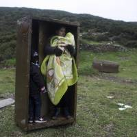 A Syrian woman with her children takes shelter in an iron box during rain Wednesday, after they arrived from Turkey to the Greek deserted island of Pasas near Chios. Thousands of migrants and refugees continue to reach Greece's shores despite the winter weather. | AP