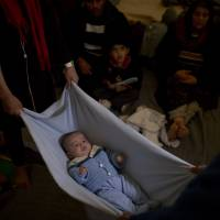 An Afghan couple use a blanket Jan. 13 to calm their baby inside the Souda camp on Chios island, Greece. Chios, an island of 50,000 residents, saw the second-largest number of arrivals in 2015, behind its northern neighbor Lesbos, where about half of all asylum-seekers landed. | AP
