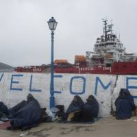 Refugees and migrants are covered with sleeping bangs during rain Wednesday on the Greek island of Oinousses, as at the background is docked a large privately owned tug converted into a rescue boat to transport them to Chios island. | AP