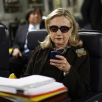 Then-Secretary of State Hillary Clinton checks her Blackberry from a desk inside a C-17 military plane upon her departure from Malta, in the Mediterranean Sea, for Tripoli in October 2011. The Obama administration confirmed Friday for the first time that Clinton's unsecured home server contained some closely guarded secrets, including material requiring one of the highest levels of classification. | AP