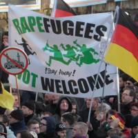 Right-wing demonstrators hold a banner reading, 'Rapefugees not welcome — !Stay away!' and a sign with a crossed-out mosque as they march in Cologne, Germany, on Saturday in the aftermath of a string of New Year's Eve sexual assaults and robberies in Cologne blamed largely on foreigners. | AP