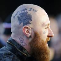 A supporter of the anti-immigration right-wing movement Patriotic Europeans Against the Islamization of the West (PEGIDA) takes part in a demonstration in reaction to assaults on women on New Year's Eve in Cologne, Germany, on Saturday. His head tattoo reads 'proud and free' and the word 'Nazi' is struck out on his neck. | REUTERS