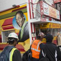 People walk past a mural of comedian Bill Cosby and U.S. President Barack Obama on the side of Ben's Chili Bowl restaurant in Washington, D.C., Thursday. Cosby has long been linked with the iconic DC restaurant and he has often attended the restaurant's events. | AFP-JIJI