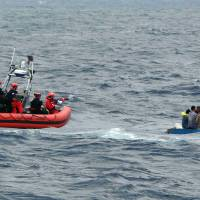 U.S. Coast Guard personnel try to assist a group of Cuban migrants on a makeshift vessel Jan. 4 in the Florida Straits. The U.S. Coast Guard says it's documenting increasing instances of violence and noncompliance at sea among Cuban migrants. | U.S. COAST GUARD VIA AP