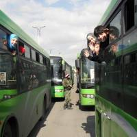 Displaced Syrian children wave from inside buses as they wait in Damascus to return to their homes in the rebel stronghold of Qadam, on the southern outskirts of the capital, on Wednesday.   AFP-JIJI