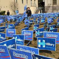 Signs supporting Democratic presidential candidates Bernie Sanders and Hillary Clinton are seen before the start of the NBC News-YouTube Democratic Candidates Debate on Sunday at the Gaillard Center in Charleston, South Carolina.   AFP-JIJI