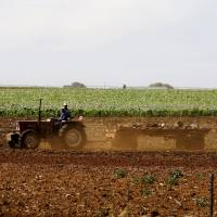 South African corn farmers work the land on Nov. 26 outside Lichtenburg. The country may need to import grain because of a drought. | REUTERS